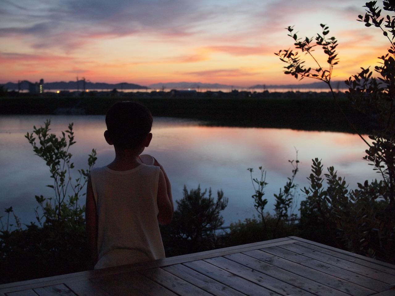画像: 夕暮れどき。海の向こうは瀬戸内の島々。さえぎる建物がない庭にさわやかな潮風が届きます。風が止んでいれば池が鏡となり、映り込んだ夕焼けの美しさにうっとりします