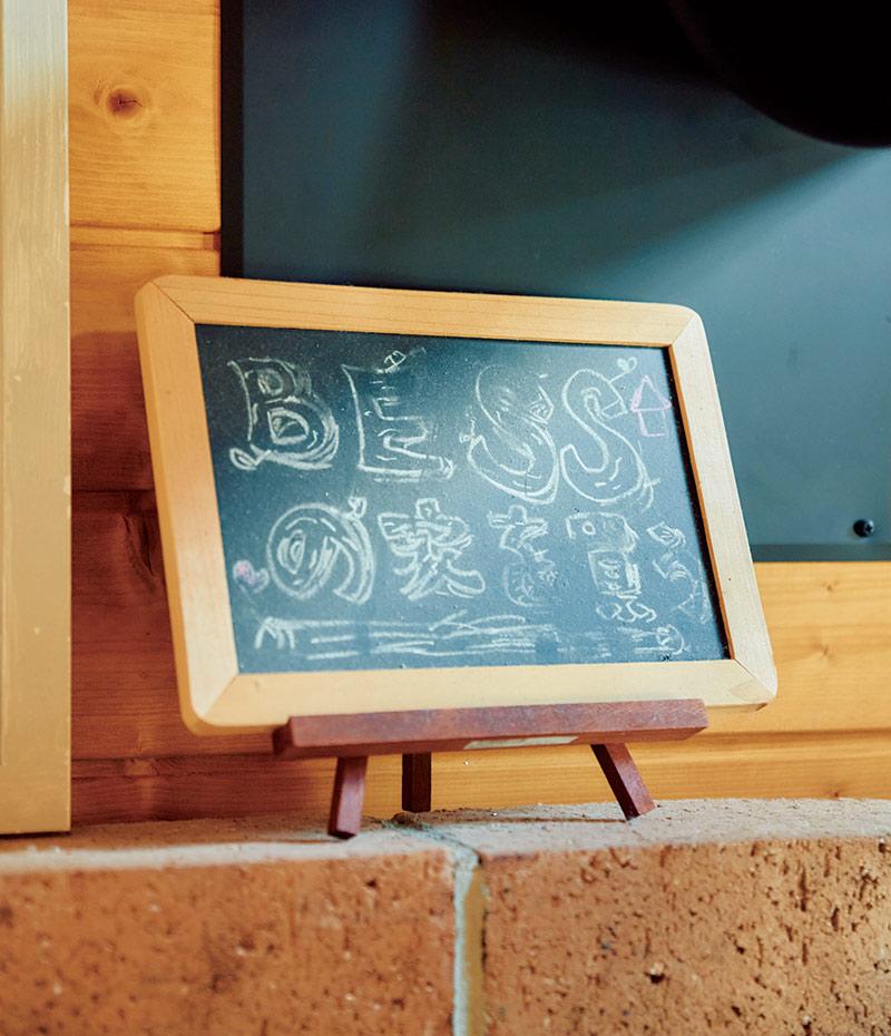 画像: 「BESSの家を買う」の黒板はいまも大事に飾っている。「夢は書くとかなうと聞いて。この家にしてよかったなと毎日思っています」
