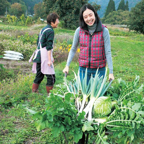 画像: 赤倉家の畑で、野菜の収穫も体験させてもらった長谷川さん。野菜を入れた手押し車を押しながら、「楽しかった」と、にっこり