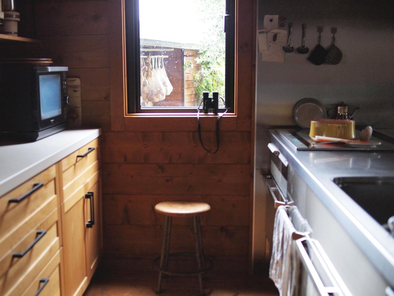 画像: コンロ側の窓から庭の軒下の玉ねぎストックが見えます。ここで椅子に腰かけ調理中のお鍋を見つつ、双眼鏡でじっくり野鳥観察することも