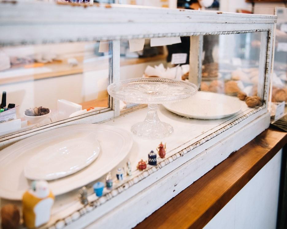 画像: レジ脇にあるアンティークの棚は、普段は器の収納に使われていますが、年末年始にはベラベッカ、シュトーレン、ガレット・デ・ロワといった、クリスマスと年始のお菓子が並びます