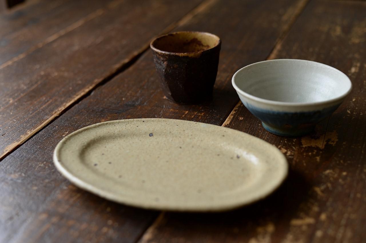 画像: 益子の土と釉薬を使い、土味を生かした器をつくる及川さん。手前から右回りに「オーバル皿」「しのぎカップ」「呉須飯碗」