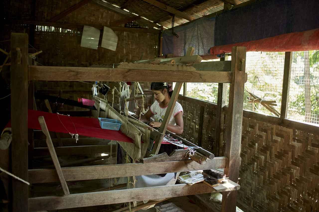 画像: 伝統化粧を施した女性が静かに布を織り進めています