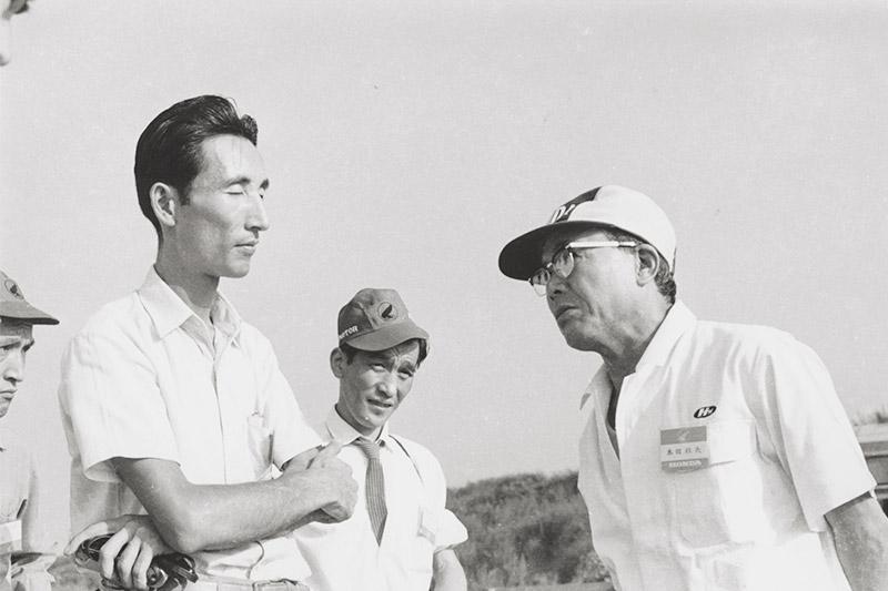 画像: ホンダ初の4輪スポーツカー、S500の試乗会が行われた荒川テストコース(当時)にて。カーグラフィック創設者の小林章太郎さん(左から2人目)と、語り合う本田宗一郎さん(右)。一般社員と同じ「白い作業着」姿の本田さんの写真は多く残されていますが、そのことはいかに氏が現場にいることを愛したかの証左なのかもしれません。 www.honda.co.jp