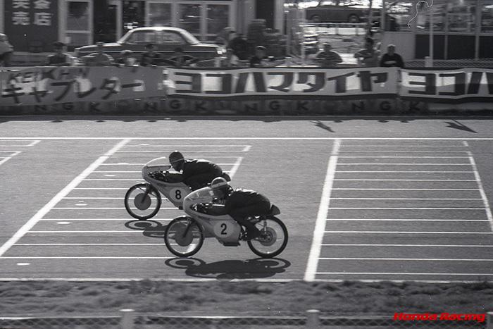 画像: 1965年最終戦となった日本GP(鈴鹿サーキット)50ccクラスで、1-2フィニッシュを決めたL.タベリ(奥)とR.ブライアンズ(手前)。この年のRC115(2気筒DOHC4バルブ)は13.6ps/20,500rpmという最高出力を誇り、ブライアンズとタベリの2人が7戦中5勝という好成績を残しました。 www.honda.co.jp