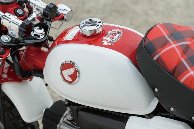 画像: タンク上面サイドの立体エンブレムと同じデザインの記念ステッカーが貼られている。復刻デザインのウイングマークバッジの外縁にも「MONKEY 50th ANNIVERSARY」の文字が。