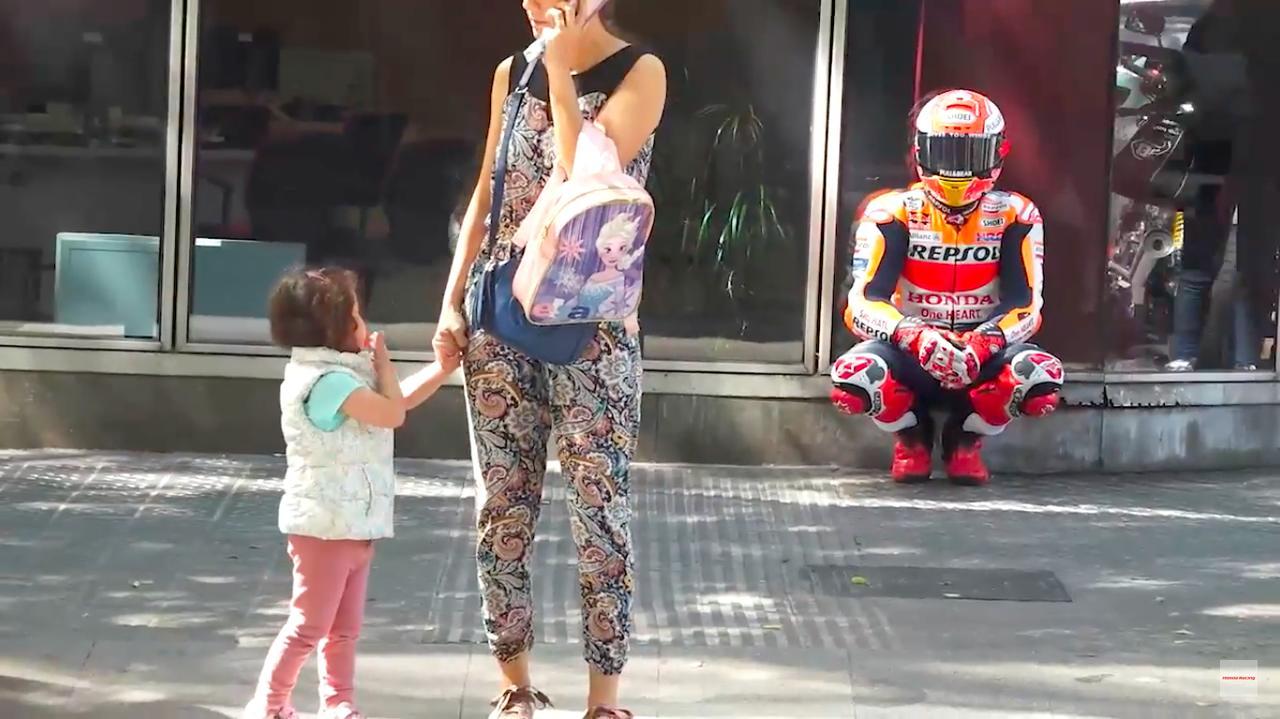画像: 道端でひと休みするM.マルケス・・・。子供が不思議そうな顔をして、その様子を見つめています(笑)。 www.youtube.com
