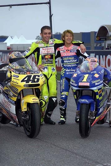 画像: タイトル獲得後のセレモニーにて。2001年500cc王者のバレンティーノ・ロッシ(ホンダ、左)と肩を組む加藤大治郎。 www.honda.co.jp