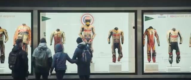 画像: 舞台はスペイン・マドリッド・・・ショーウインドウに、GPライダーたちが着用したレザースーツなどが陳列されています。 www.youtube.com