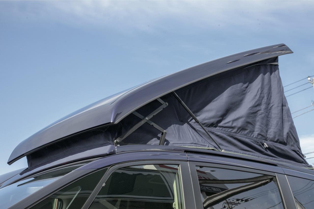 画像: 車両のルーフ形状に合わせて作られたポップアップルーフ。風切り音を抑えて、快適性や燃費性能を悪化させない工夫がなされている。ダンパーとパンタグラフで、比較的軽い力で開閉可能