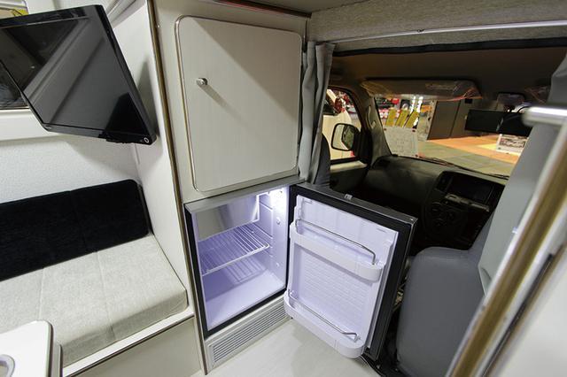 画像: 助手席後側にはオプションで冷蔵庫を装備することができる。冷蔵庫の上部と通路を挟んだ反対側は物入れになっていて重宝しそう。