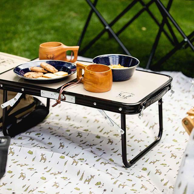 画像: 持ち運びしやすい2つ折りテーブル。折りたたんだ際、テーブルの内側にレジャーシートなどの小物を収納できる。ミニテーブル 3,850円。