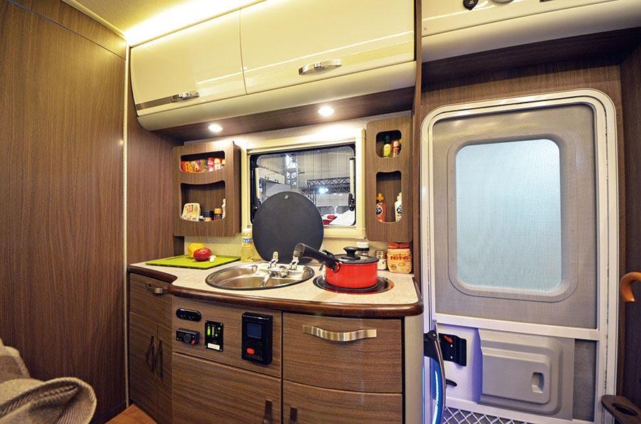 画像: エントランスと横にキッチンスペースがある。コンロにはIHヒーターを採用。温度設定モニターが付いたボイラーでお湯も利用できる。給水タンクは135L。