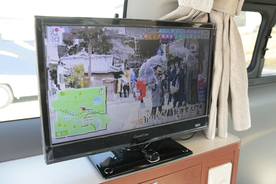 画像: 後部のテレビには別途チューナーが付属。チャンネル設定を、旅先で随時する必要はなく、電波を自動感知して変更。インパネのテレビとは連動していない。