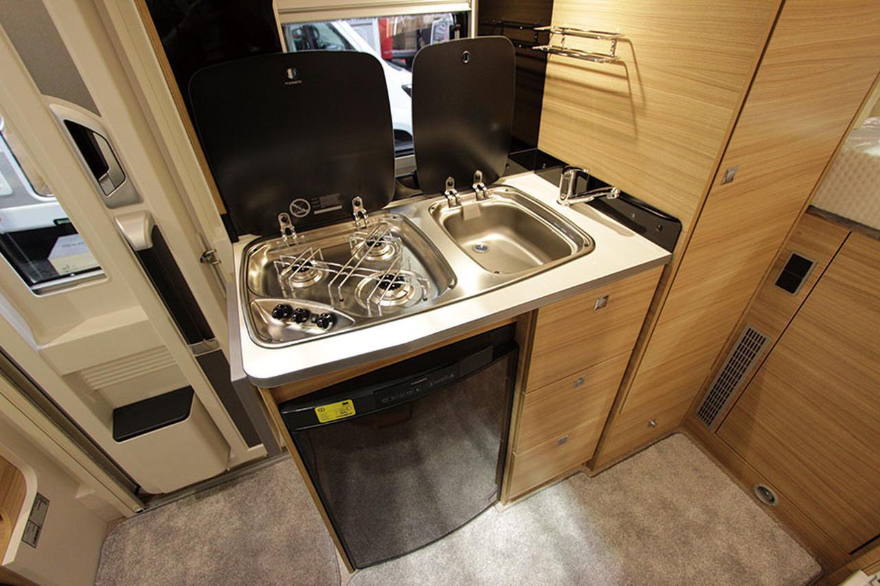 画像: キッチンには3口コンロ、シンクを装備。コンロの左側にはフォールディングテーブルを備え、広げることでキッチンスペースが拡大する。