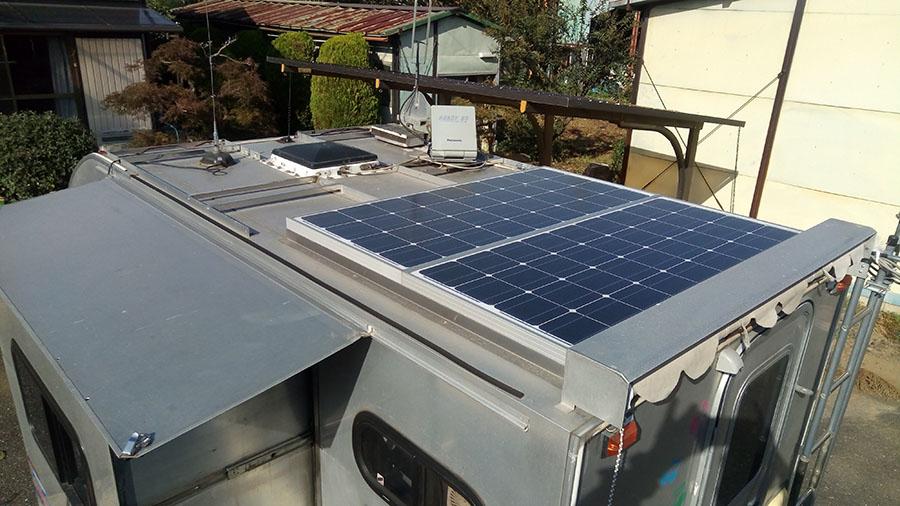 画像: スバル・サンバーのルーフには100Wのソーラーパネルを2基設置。車内にはインバーターとリチウムイオンバッテリーも装備しているのだ。
