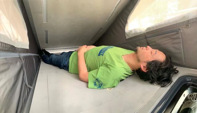 画像: NV200ベースのキャンピングカー、キャネルで就寝。これは撮影用で斜めに寝たもの。本当はまっすぐに寝られるし、かなり広々している。