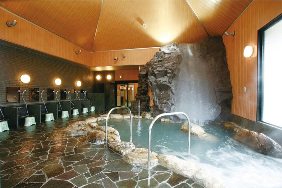 画像: 「森の国ぽっぽ温泉」はJR予土線・松丸駅の2階にある天然温泉施設。写真は滑床渓谷の雪輪の滝をイメージした岩風呂調の浴室。写真/森の国ぽっぽ温泉
