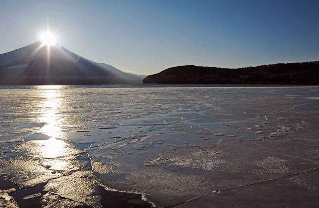 画像: 山中湖に張った氷に光の矢を放つ、夕暮れのダイヤモンド富士。