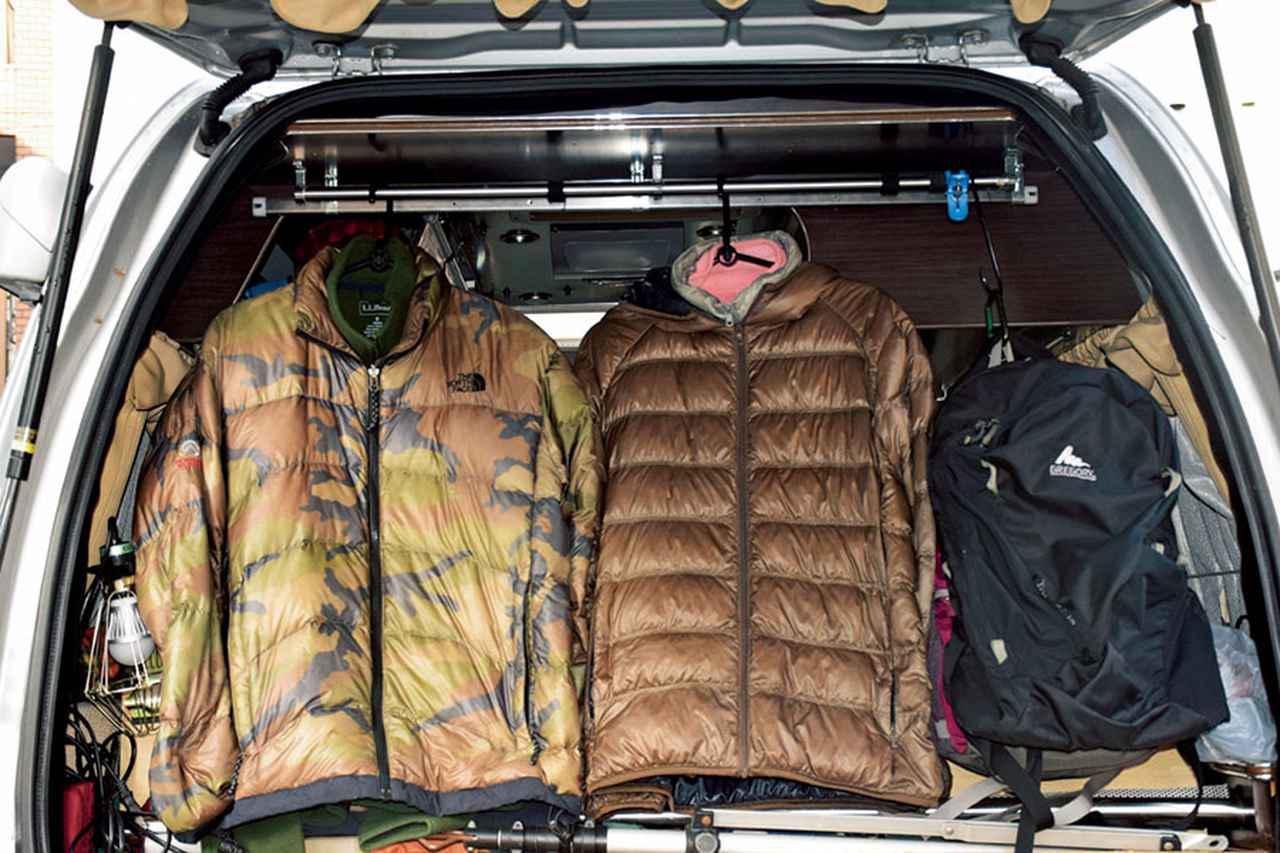 画像: スキーやスノーボードの分厚いウエアも、バックドア付近にポールで吊るせば、かさばらないだけでなく着替えも楽になります。車内に雪が降り込むのを防ぐ効果も。