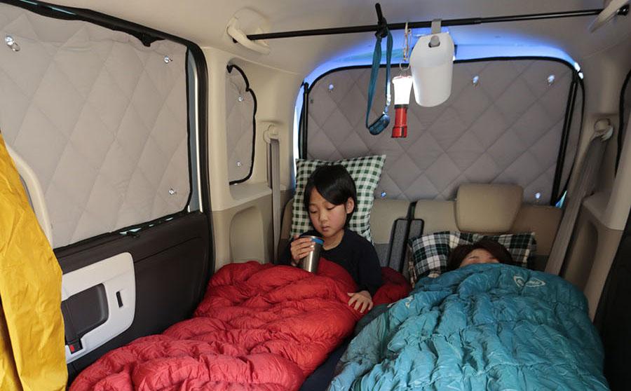 画像: 実際に車中泊をしてみると気づくことも多い。写真はホンダ・N‐BOXの車内。軽自動車で家族4人は寝られない。2名が限界だろう。