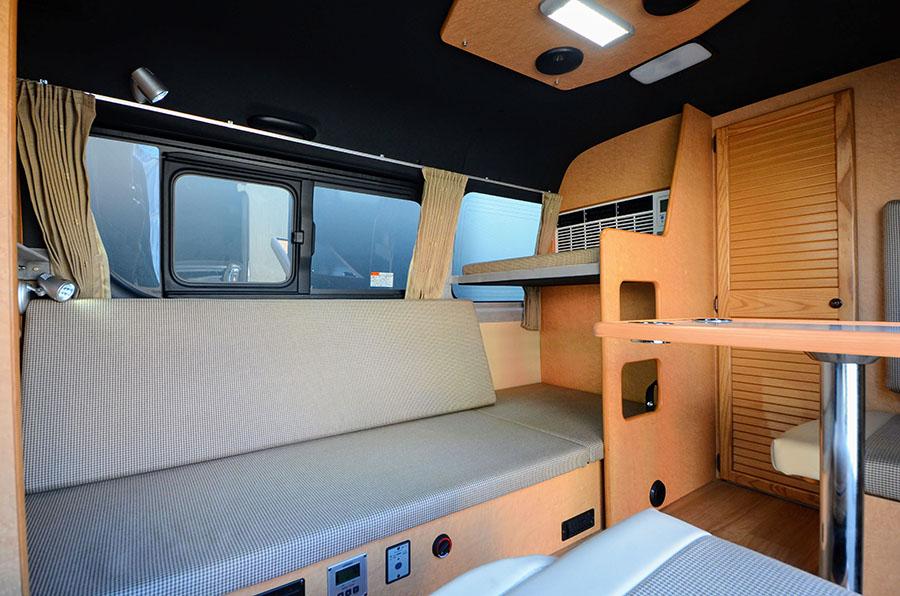 画像: 常設2段ベッドを展開すると、ベンチシートになる。対座シートと合わせれば、テーブルを囲んだリビングレイアウトに。上段の床板は3分割になっていて、簡単にレイアウト変更できる。走行中もベンチシートとして利用できるので便利だ。