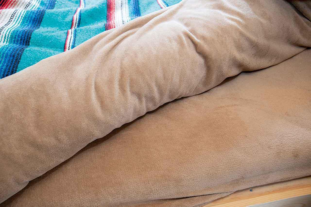 画像: 車内で最も効果の高かった寒さ対策が寝具だった。羽毛布団と発熱機能を持つカバーで、寒くても布団に潜り込めば、快適に寝られるという。