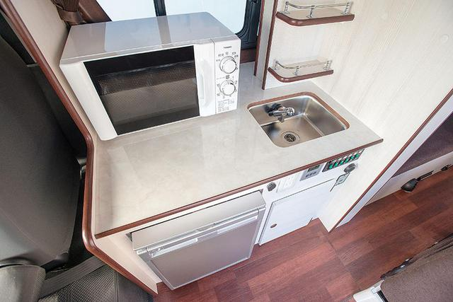 画像: キッチンはコンパクトにまとめられた。電子レンジを置いても作業スペースを確保している。