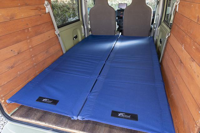 画像: 親子で車中泊キャンプに行くことも多いという。そのときは室内にキャンプ用のコットを2つ置いて、フラットな床を作る。偶然にも、コットのサイズがクルマの荷室と同じサイズだった。