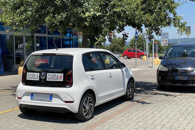 画像: SCUOLA GUIDAとは自動車教習所を表し、そのステッカーが貼られているのは教習車である。2020年夏、イタリア中部シエナ県にて。