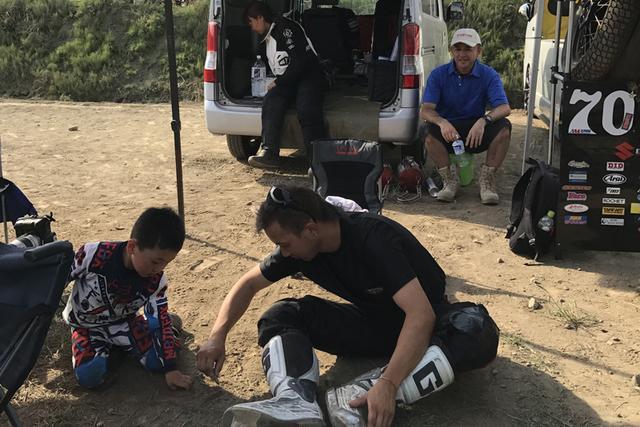 画像: 2017シーズン第2戦のパドック風景。motoGPのスーパースター、M・マルケスが認めるワールドクラスダートトラッカー・FEVHOTS70大森雅俊が、キッズクラス参加のライダーと走行の合間に砂遊び。撮影: FEVHOTS
