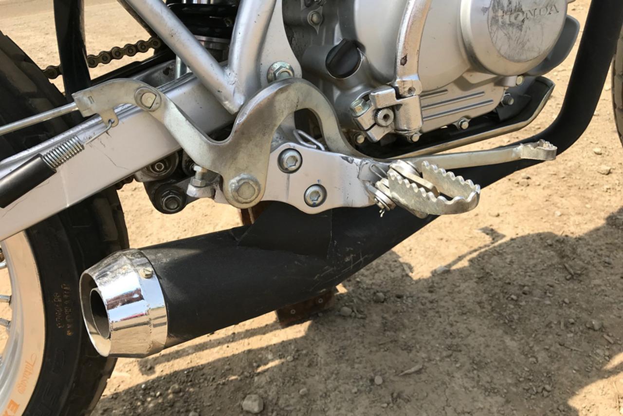 """画像: リアブレーキペダルはフルバンク旋回中にも容易に踏み込めるよう、フットペグより低い位置がマスト。ドラムハブ側でも調整し、""""どこまで踏んでもロックしない"""" ギリギリの案配が扱いやすい。サイレンサーはヒャク用のアメリカ製ダートトラックマフラーを選び、新造したエキゾーストパイプと合わせて装着。ダウンマフラーはリアタイヤやリアショックからの路面の情報がより多く得られ、非力な軽量級でも大変有効なカスタマイズ。"""