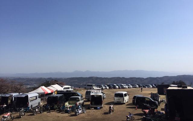 画像: 芝生のラジコン飛行場を取り囲むように駐車するパドックスペース。左手後方が高崎市中心部方向。新たに作られたショートトラックは、ここから丘を少し登ったレベルに位置する。撮影: ロデオモーターサイクル