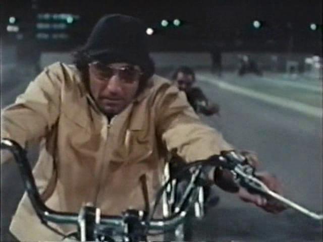 """画像: 1970年公開のアメリカ映画 """"C.C. and Company"""" (邦題は""""C.C.ライダー"""") のクライマックスシーンでは、元フットボール選手で主演のジョー・ネイマスと、対立する暴走族リーダー・ムーンとの """"ノーヘル普段着チョッパー同士"""" による陸上競技場?かフットボール場?での生命を賭けたオーバルトラック対決を見ることができます。"""