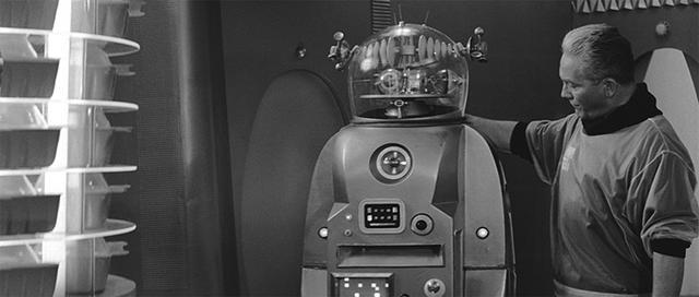 """画像: 船員のひとりが、相棒として旧型の喋るロボット""""パトリック""""を連れている"""