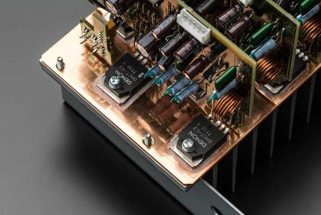 画像: パワーアンプ部の出力素子には、サンケン電気との共同製作によるDHCT(Denon High Current Transistor)を搭載。アイドリング精度を向上させるためにアイドリング電流補償用のデバイスを内蔵しており、瞬時の大電流出力にも安定して応えられるという。さらに発熱対策として、ヒートシンクの裏側(写真で見えている部分)には銅板を使って熱を逃している。これは同社の2chオーディオ製品でも使われる手法で、AVセンターでは初採用だ
