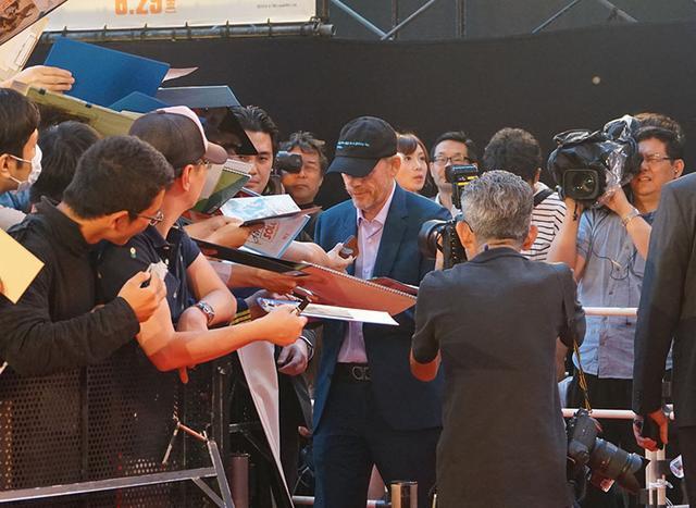 画像: ファンが差し出したチラシやグッズにていねいにサインをしていた
