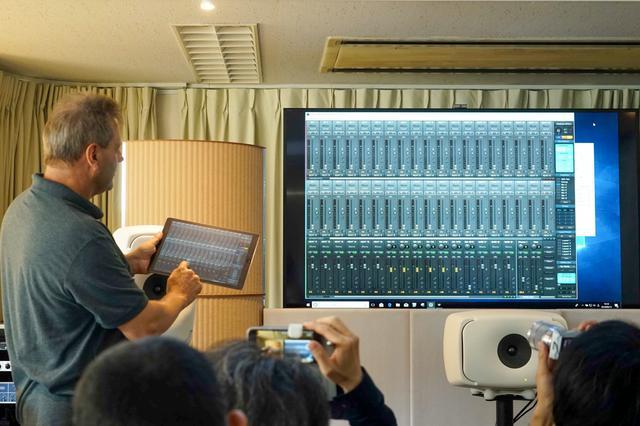 画像: (奥のディスプレイで表示されている)PC上で動作するTotal Mixを、iPadアプリ「Total Mix Remote」で操作しているデモ風景。操作は、ドイツRMEから来日した同社創業者で開発者のマティアス・カーステンズ氏