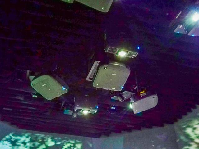 画像: 天井には多くのプロジェクターが設置される。複数の種類の製品が、あらゆる角度に投写できるように置かれていることがわかるだろうか