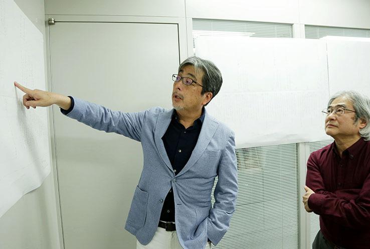 画像: 壁に貼られた35年分のハード年表を見ながら、画質について話しをする山本さん(左)と吉田さん(右)