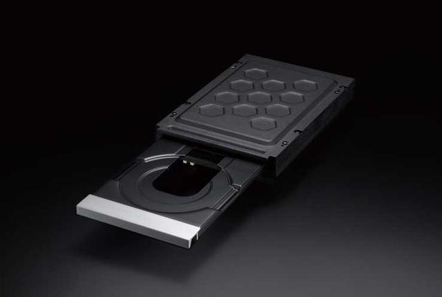 画像: 制振効果があるという黒塗装を施したハニカムメカカバーのシールドで覆われるディスクドライブを搭載。メカベースは減衰性の高いパルプ素材を挟み込む形でフローティングさせて固定している。これはドライブ内外で発生する振動の抑制と、ディスクドライブ搭載機では重要なポイントとなるドライブ自体の静音性の向上に寄与しているそうだ。ディスクトレイは高剛性で安定性の高いアルミダイキャスト製だ