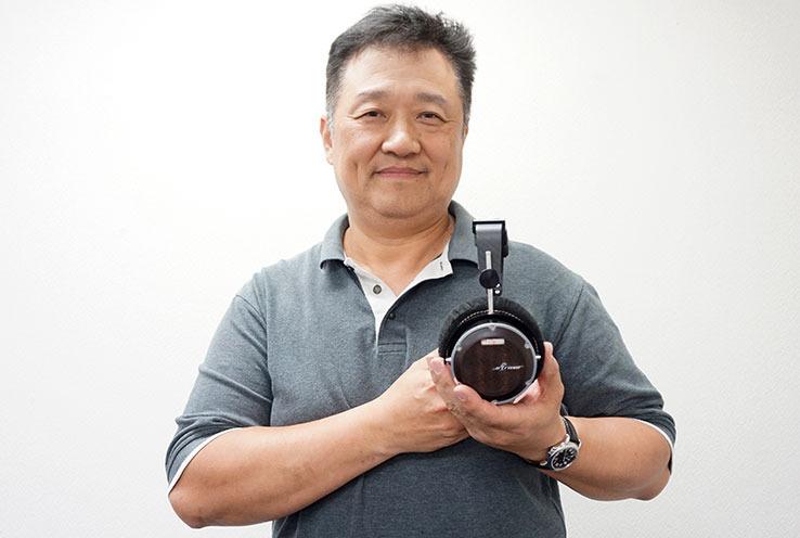 画像: 5月に発売された最新ヘッドホン「Signature」(¥640,000+税)を手にポーズ。硬く粘りが強いという台湾アカシアという木材を用いている