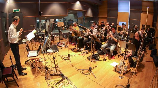 画像: 角田健一ビッグバンドのレコーディング風景。別ブースのドラム、ベースも一緒に演奏するのだが、角田氏の合図を確認できるよう鏡が置かれている