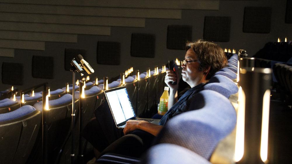画像: 音響監修をする岩浪音響監督。測定器のほか、ノートPCでメモをとって音響のチェックを行なっている