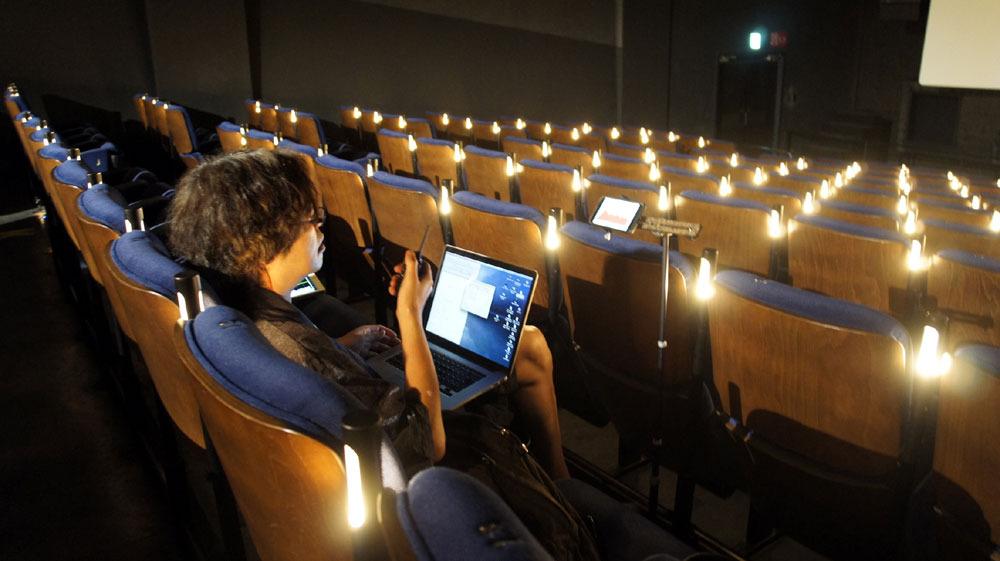 画像: 音響チェックを行なう岩浪さん。手に持っているのはトランシーバーで、上映室にいるスタッフとやりとりをしている