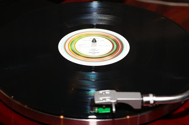 画像: 回転するレコード盤の上にレコード針を落とすと、溝に刻まれた信号を拾って、音楽が流れだす