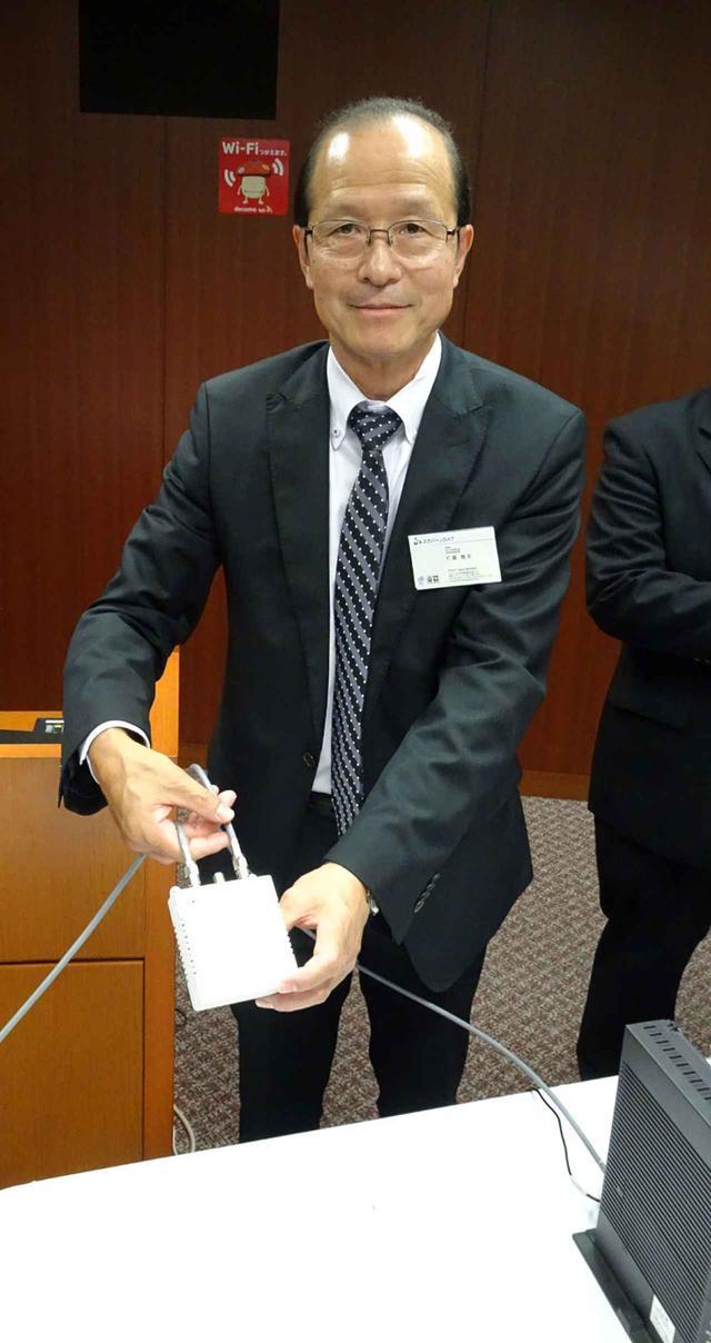 画像: 専用アダプターを手にするスカパーJSAT 仁藤雅夫 取締役 執行役員副社長