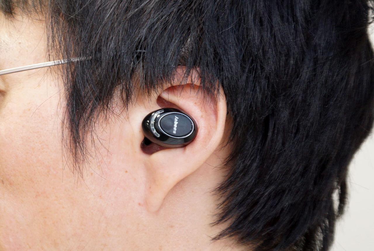 画像: 装着イメージ。耳たぶに収まるコンパクトさだ。ロゴ近くの突起部をクリックして操作する。右イヤホンはアンビエントモード、左はSiriやGoogle Assistantの呼び出しだ