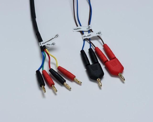 画像: スピーカーを接続するケーブルは7.2.4構成のすべてがバナナプラグという仕様(写真はセンタースピーカーとサブウーファー用のスピーカープラグ)。センタースピーカーは左右2本使いのため、AVセンターに接続する際は付属の分岐プラグを用いる。また、サブウーファーはパッシブ型のため外部のアンプが必要となる