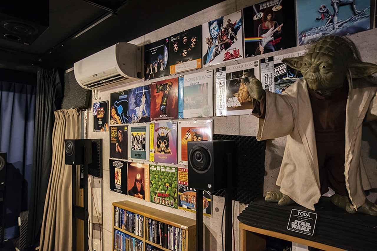 画像: 視聴位置右側の壁面にはUHDブルーレイ等を収めたソフトラックを配置し、その上側にお気に入りのLDジャケットをディスプレイ。写真のスピーカーはフロントワイドとサラウンドの右チャンネル